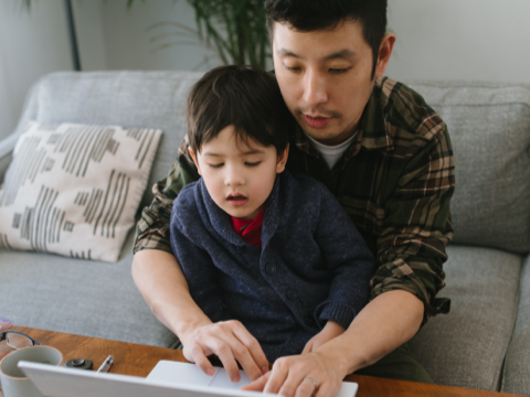 Man and child sitting in front of a laptop