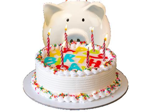 Piggy bank siting behind a birthday cake