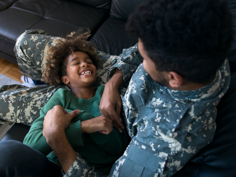 Service member sitting with child