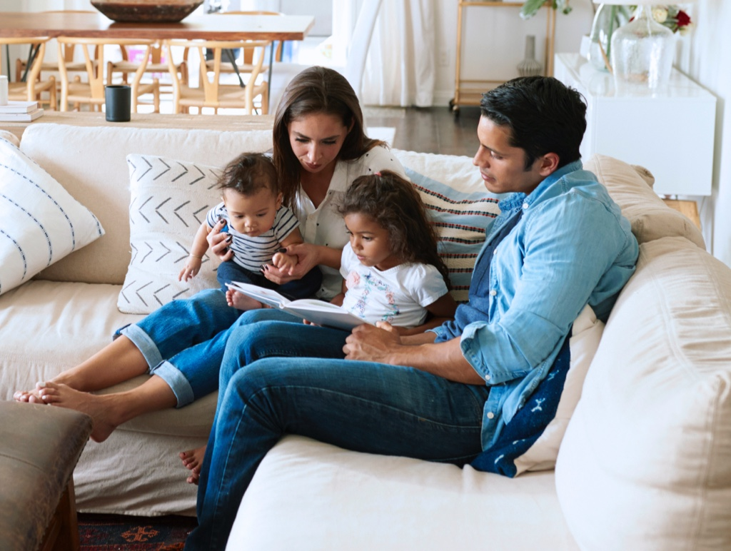family on a couch reading a book